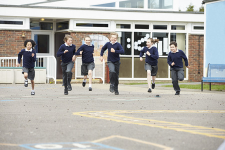 Photo for Group Of Elementary School Pupils Running In Playground - Royalty Free Image