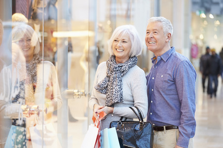 Photo pour Happy Senior Couple Carrying Bags In Shopping Mall - image libre de droit