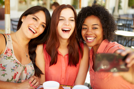 Photo for Three Female Friends Taking Selfie In CafŽ - Royalty Free Image
