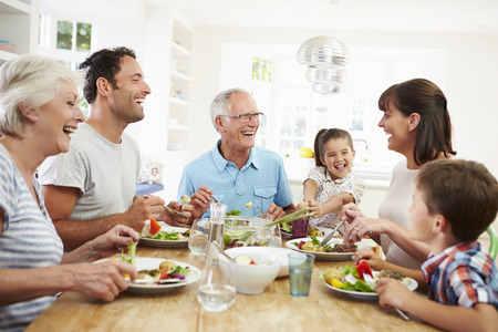 Foto de Multi Generation Family Eating Meal Around Kitchen Table - Imagen libre de derechos