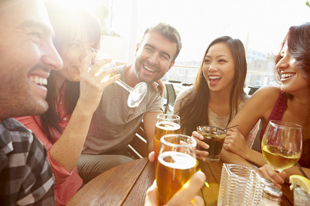 Photo for Group Of Friends Enjoying Drink At Outdoor Rooftop Bar - Royalty Free Image