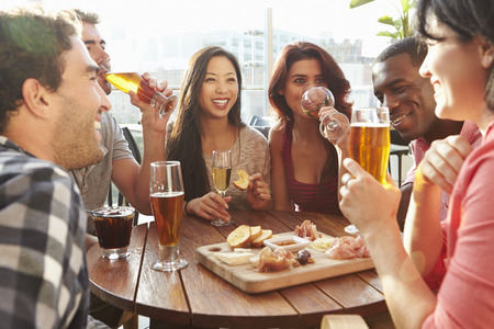 Photo for Group Of Friends Enjoying Drink And Snack In Rooftop Bar - Royalty Free Image