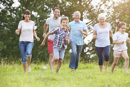 Photo for Multi Generation Family Running Across Field Together - Royalty Free Image