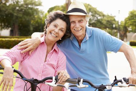 Photo pour Senior Hispanic Couple Riding Bikes In Park - image libre de droit