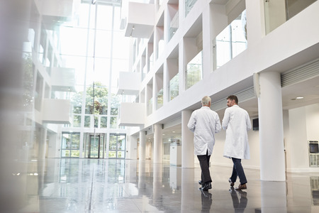 Photo for Rear View Of Doctors Talking As They Walk Through Hospital - Royalty Free Image