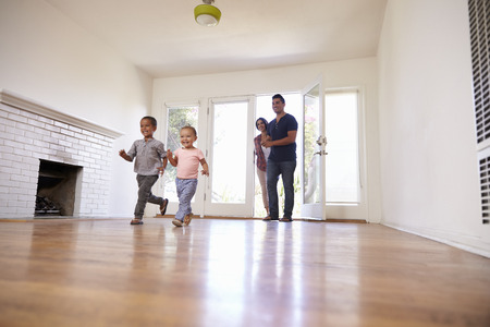 Photo for Excited Family Explore New Home On Moving Day - Royalty Free Image