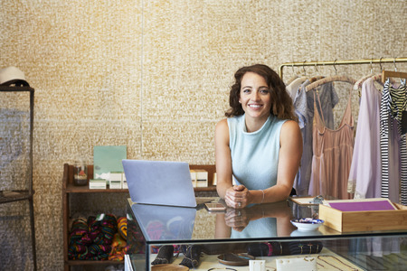 Photo for Young woman working in clothes shop leaning on counter - Royalty Free Image