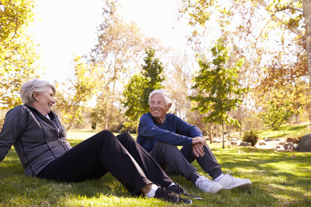 Senior Couple Resting After Exercising In Park Together