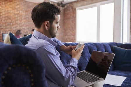 Businessman Working On Sofa In Modern Creative Office
