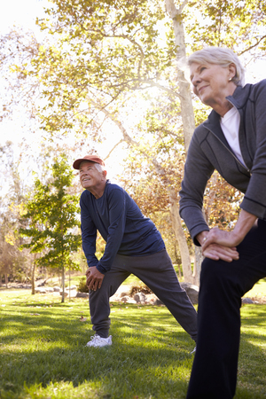 Senior Couple Stretching Whilst Exercising Together In Park