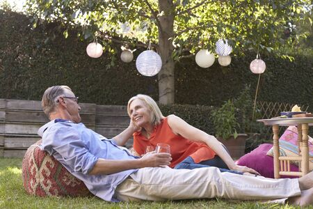 Mature Couple Enjoying Drinks In Backyard Together