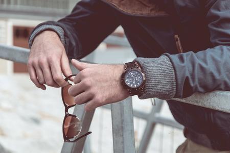 Foto de Luxury men's watch and fancy sunglasses in man hands - Imagen libre de derechos