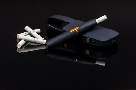 Foto de PElectronic cigarette, tobacco heating system  on black background - Imagen libre de derechos