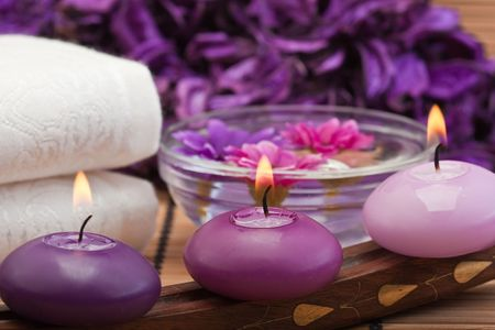 three purple toned candles and flowers in spa setting (1)