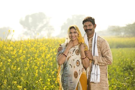 Photo pour Rural couple standing in rapeseed field - image libre de droit