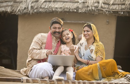 Photo pour Rural Indian family using laptop on traditional bed at village - image libre de droit
