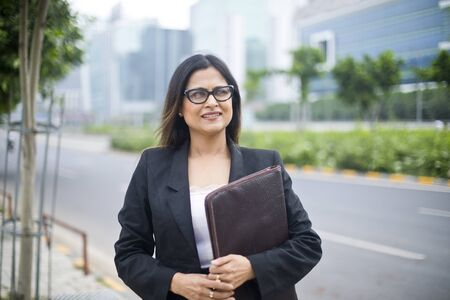 Photo for Young Indian businesswoman with a file in city - Royalty Free Image