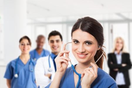 Foto de Portrait of a smiling nurse in front of a medical team - Imagen libre de derechos