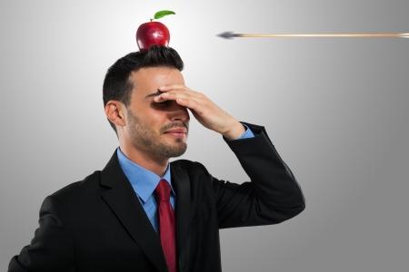 Photo pour Risk management concept, arrow hitting an apple on a businessman's head - image libre de droit