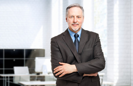 Foto de Mature businessman portrait in his office - Imagen libre de derechos