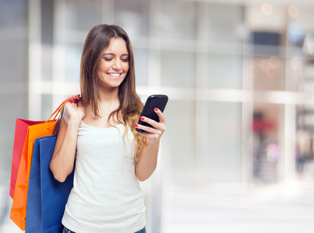 Photo pour Young woman holding shopping bags and a mobile phone - image libre de droit