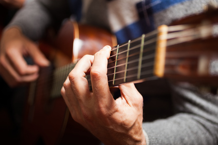Photo pour Detail of a guitarist playing a classical guitar - image libre de droit