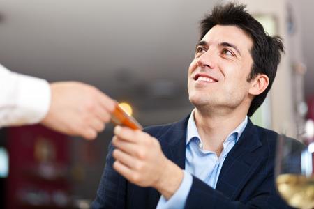Photo pour Man paying dinner in a restaurant - image libre de droit