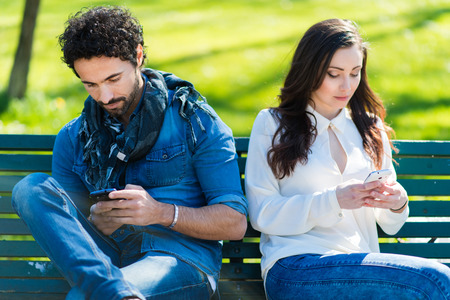Photo pour Couple not talking to each other typing on mobile phones - image libre de droit