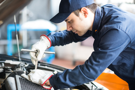 Photo pour Portrait of an auto mechanic at work on a car in his garage - image libre de droit
