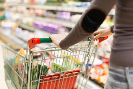 Photo pour Woman grocery shopping in a supermarket - image libre de droit