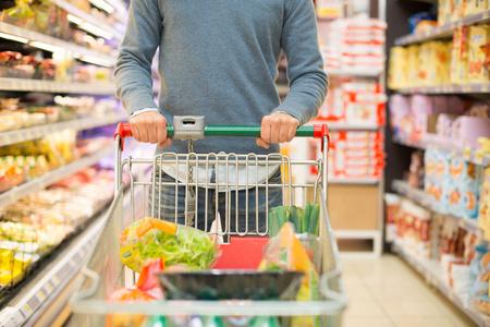 Photo pour Close-up detail of a man shopping in a supermarket - image libre de droit