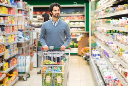 Photo pour Handsome man shopping in a supermarket - image libre de droit