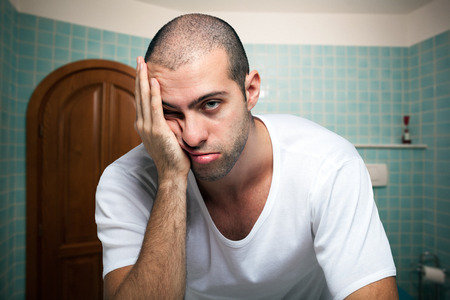 Foto de Portrait of a tired man looking in the mirror in the bathroom - Imagen libre de derechos