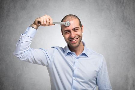 Foto de Smiling man using a wrench to adjust his mind - Imagen libre de derechos