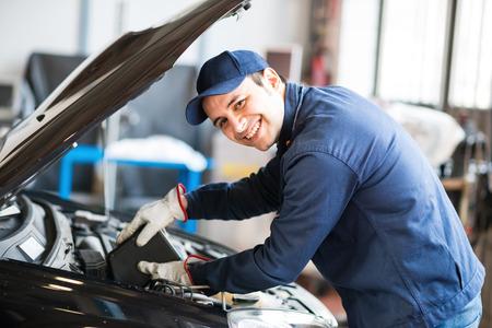 Photo pour Portrait of an auto mechanic putting oil in a car engine - image libre de droit