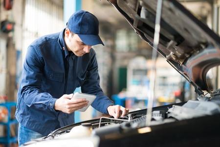 Foto de Portrait of a mechanic using a tablet in his garage - Imagen libre de derechos