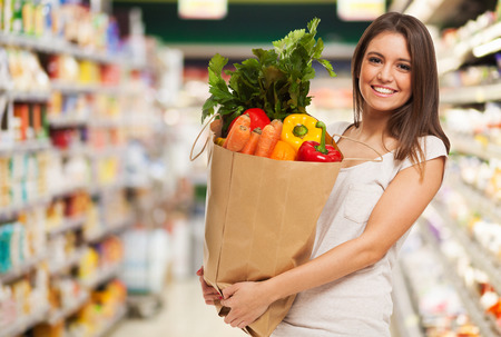 Photo pour Healthy positive happy woman holding a paper shopping bag full of fruit and vegetables - image libre de droit