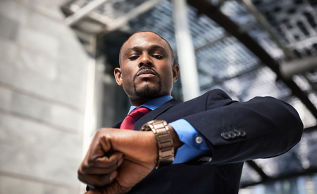 Photo pour Handsome businessman looking at his watch - image libre de droit