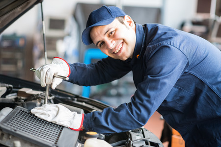 Photo pour Portrait of a smiling fixing a car engine in his garage - image libre de droit