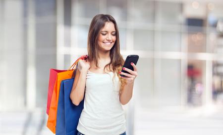 Foto de Young woman holding shopping bags and a mobile phone - Imagen libre de derechos