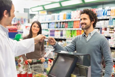 Foto de Customer using a credit card to pay in a supermarket - Imagen libre de derechos