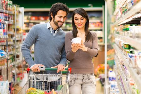 Photo pour Young couple shopping in a supermarket - image libre de droit