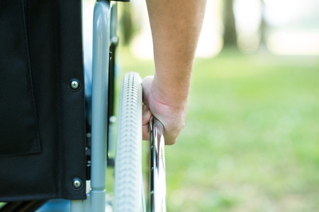 Foto de Detail of a man using a wheelchair in a park - Imagen libre de derechos