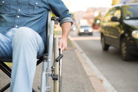 Photo pour Detail of a man using a wheelchair in an urban street - image libre de droit
