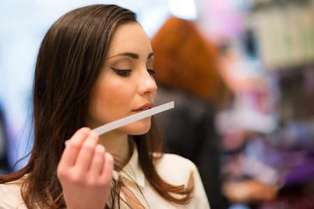 Foto de Woman smelling a perfume tester in a shop - Imagen libre de derechos