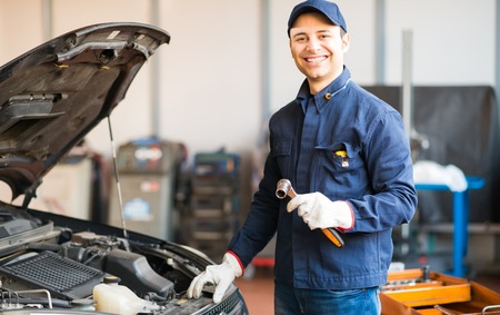 Photo pour Mechanic holding a wrench while fixing a car in his shop - image libre de droit