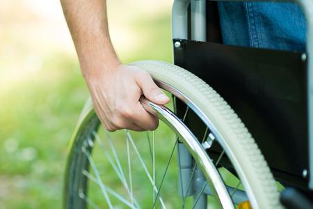 Photo pour Detail of a man using a wheelchair in a park - image libre de droit