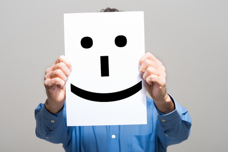 Photo for Man holding a smiling face emoticon - Royalty Free Image