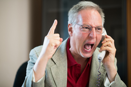 Photo pour Portrait of an angry businessman yelling at phone - image libre de droit