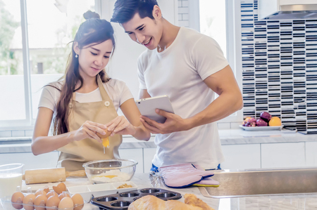 Foto de Beautiful asian young couple helping to cooking bekery in the kitchen at home.Man is looking tablet. - Imagen libre de derechos